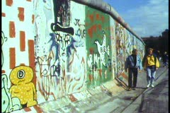 Berlin,  The Berlin Wall in 1988, people walk alongside, graffiti - stock footage