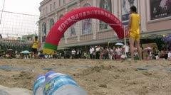 Beach volleyball game in center of city in China Stock Footage