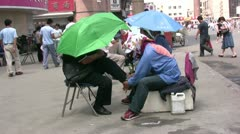 Polishing shoes on the streets in China Stock Footage