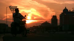 A man on a motorbike waits for his friend at sunset in Manzhouli, China Stock Footage