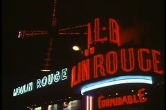 Paris, Paris at night, The Moulin Rouge, neon flashing, windmill turning Stock Footage