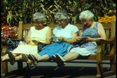 London,   Kensington Park, three women sit on bench, feet propped up - stock footage
