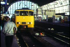 Amsterdam,  Train, yellow, arriving in the station on the platform Stock Footage