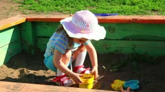 Little girl playing in sandbox Stock Footage