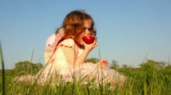 Little girl eating apple on meadow Stock Footage