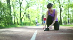 Young woman tying running shoes before run, dolly shot HD Stock Footage