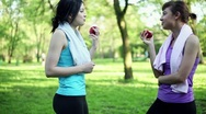 Stock Video Footage of Female friends resting and eating apple after sport workout, dolly shot HD