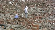 Female workers search for valuable items at a demolished quarter, China Stock Footage