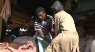 Stock Video Footage of Two African Men moving heavy bag in market warehouse