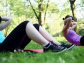 Stock Video Footage of Young women doing sit-ups, exercising in the park, dolly shot NTSC