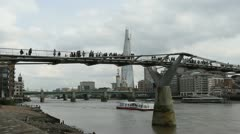 The Shard and people crossing Millennium Bridge London Stock Footage