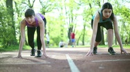 Stock Video Footage of Two young beautiful women preparing to run, dolly shot HD