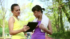 Personal trainer with tablet computer explaining how to exercise, dolly shot HD Stock Footage