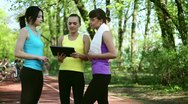 Stock Video Footage of Personal trainer with tablet computer explaining how to exercise HD
