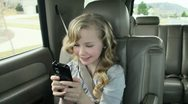 Stock Video Footage of Girl riding in the back seat of a car or SUV listening to headphones and text