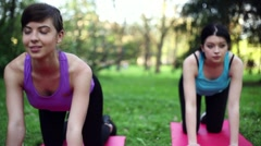 Two young women practice yoga in the park, dolly shot HD Stock Footage