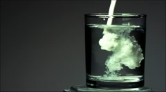 Milk is poured into a glass of water in slow motion Stock Footage