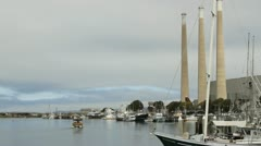 Tour boat chugs by Morro Bay populated by boats with smoke stacks along shore Stock Footage