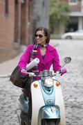 Nuori nainen ajo skootteri Kuvituskuvat