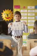 Young boy in classroom holding up graded math sheet Stock Photos