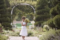 Girl standing in garden holding flowers Stock Photos