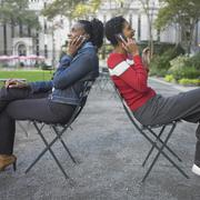 Friends talking on cell phone in park Stock Photos