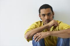 Portrait of man sitting on floor Stock Photos