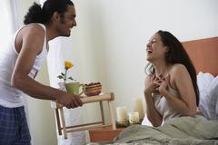 Man bringing woman breakfast in bed Stock Photos
