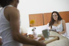 Man serving woman breakfast in bed Stock Photos