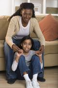 Portrait of mother and daughter sitting in living room Stock Photos