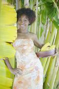 Portrait of woman standing next to banana tree holding bananas Stock Photos