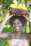 Portrait of woman smiling with bowl of bananas balanced on head Stock Photos