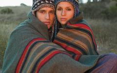 Portrait of couple in caps wrapped in a blanket Stock Photos