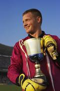 Male goalie triumphantly holding trophy Stock Photos