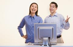 Portrait of businesspeople laughing at computer Stock Photos