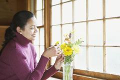 Young woman arranging flowers Stock Photos