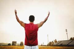 Male athlete holding his arms out on football field Stock Photos
