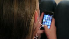 Girl playing a game on her ipod or iphone with headphones.mp4 - stock footage