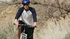 Guy riding a bike with a blue helmet 1.mp4 Stock Footage