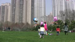 Kids in China play with kites and balloons in an urban scene - stock footage
