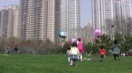Stock Video Footage of Kids in China play with kites and balloons in an urban scene