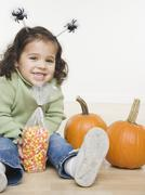 Portrait of little girl with pumpkins and candy corn Stock Photos