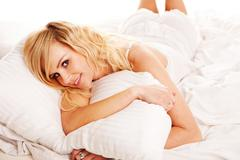 Pretty blonde hugging her pillow in the morning Stock Photos