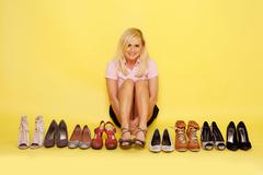 Pretty woman showing shoes collection   Stock Photos
