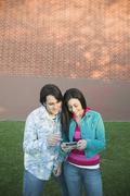Young hispanic couple looking at pda outdoors Stock Photos