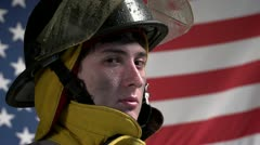 Heroic firefighter in front of US flag Stock Footage