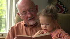 Grandfather reading to his granddaughter - stock footage