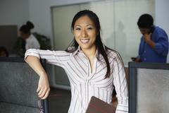 Asian businesswoman leaning on cubicle wall Stock Photos