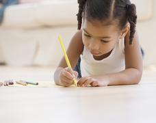 African girl coloring on floor Stock Photos
