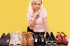 Blonde lady with a passion for shoes Stock Photos